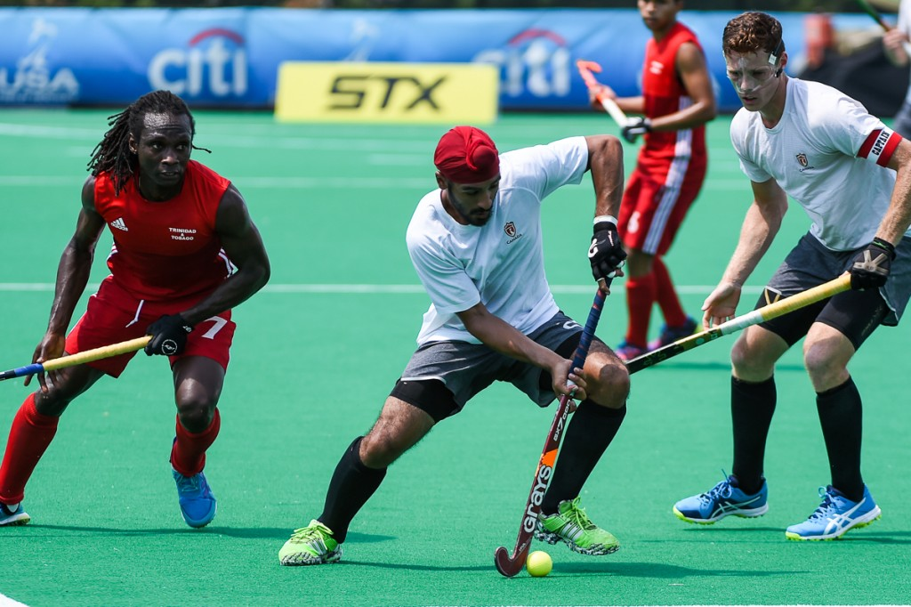 PHOTO: Harbir Sidhu (centre) carries the ball out of danger while playing Trinidad Tobago at the 2017 Pan American Cup on August 4 in Lancaster, USA. (by Yan Huckendubler/PAHF)